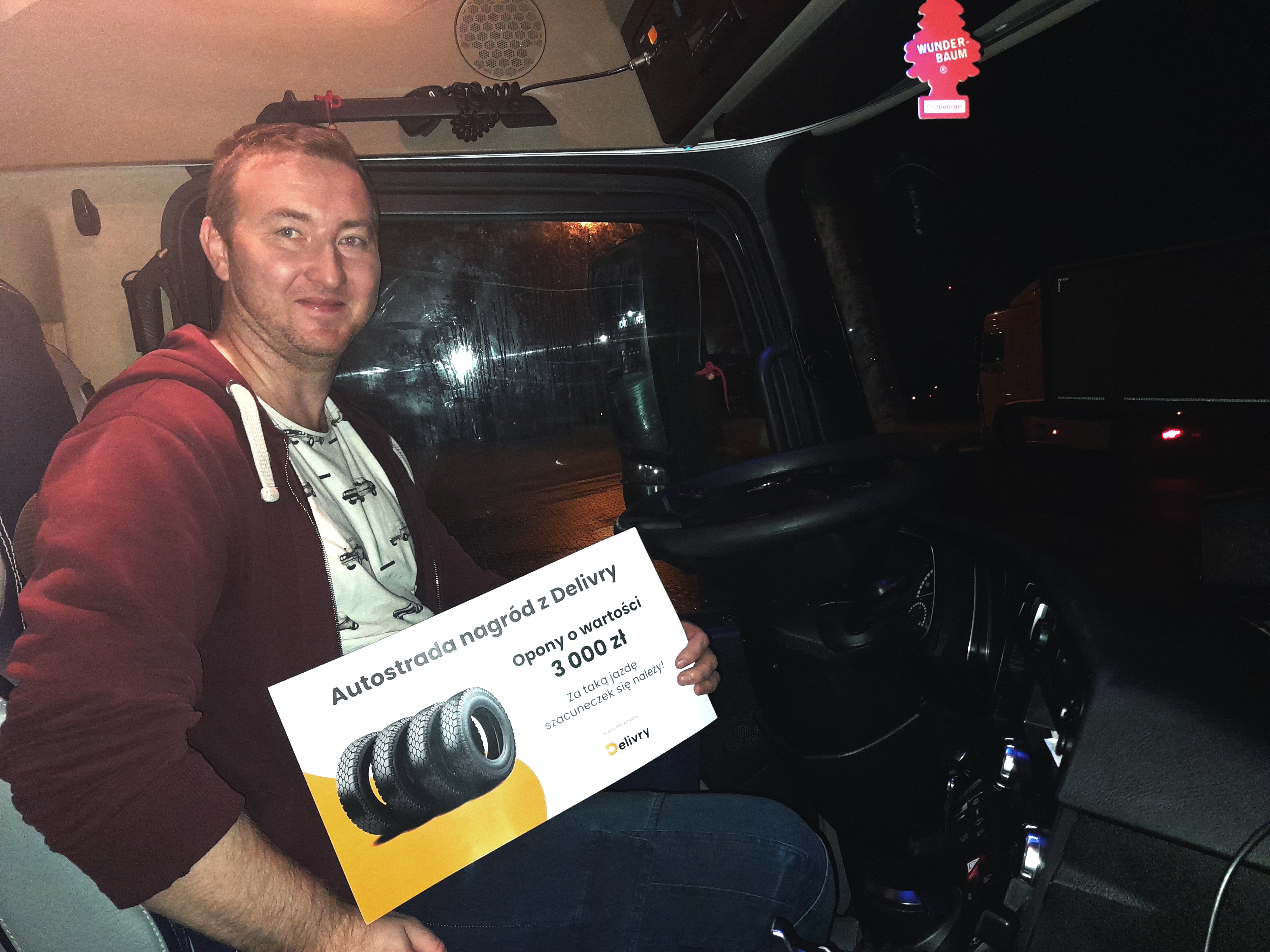 kierowca zawodowy w ciężarówce trzyma voucher z nagrodą.