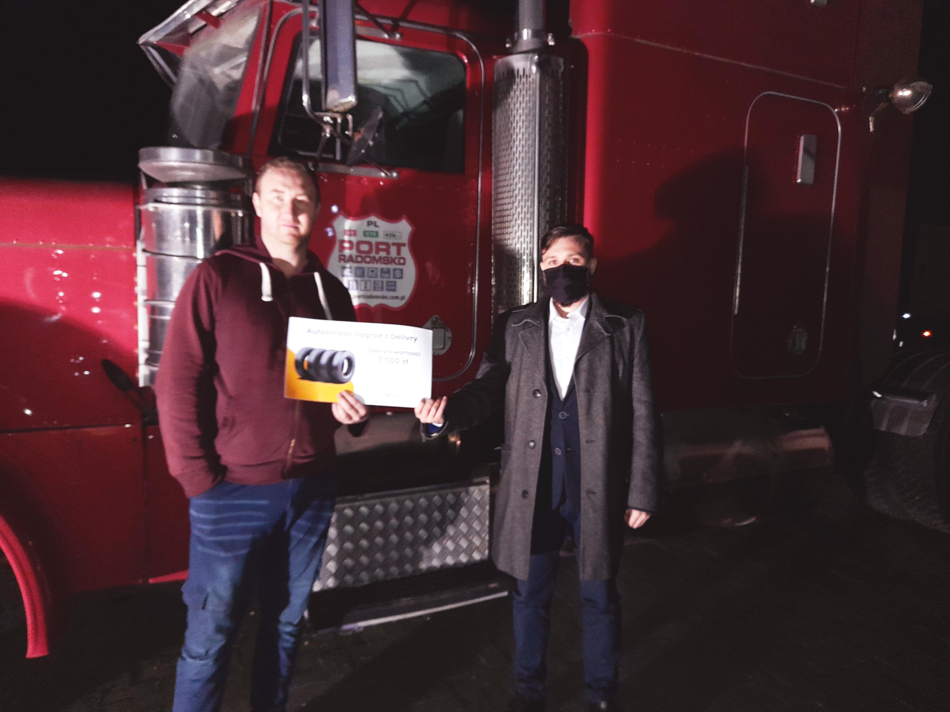 kierowca i szef sprzedaży stoją nocą przed samochodem ciężarowym w porcie Radomsko